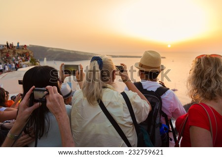 Large group of tourist watching and taking photos of famous sunset view in Oia village on Santorini island in Greece, Mediterranean Europe. - stock photo