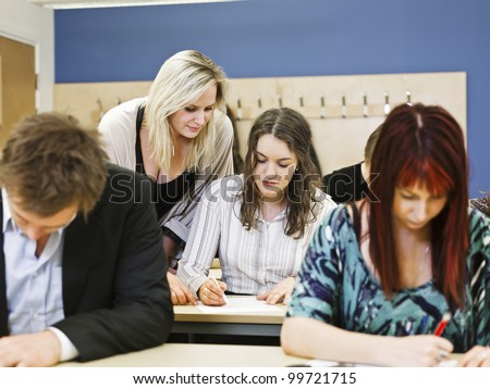Large group of young adults studying in a classroom - stock photo