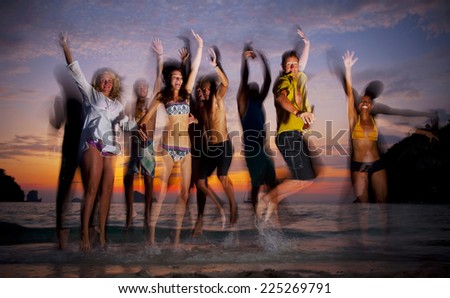 Large group of young people enjoying a beach party. - stock photo