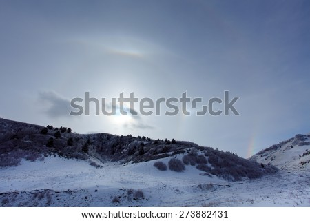 Large halo around the sun on a winter day in mountains. Hasaut village, North Caucasus, Russia. - stock photo