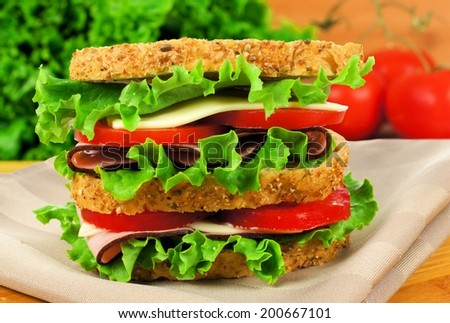 Large ham, lettuce and tomato sandwich on whole grain bread