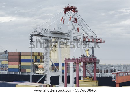 Large harbour crane loading containers on a large cargo vessel