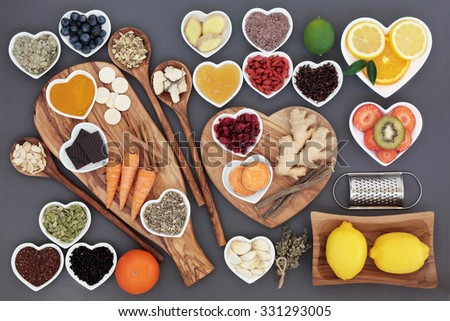 Large health food and herb selection for cold and flu remedy including foods high in antioxidants and vitamin c on olive wood boards and spoons over grey background. - stock photo