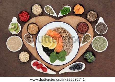 Large health food selection in bowls on a heart shaped wooden board over lokta paper background. - stock photo