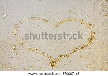 Large heart draw by hand on sand beach for St. Valentine day - stock photo
