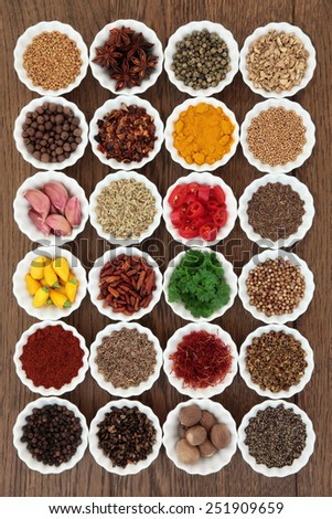 Large herb and spice selection in porcelain crinkle bowls over old oak background.   - stock photo