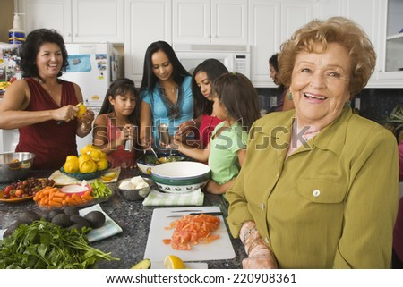 Large Hispanic family in kitchen preparing food - stock photo