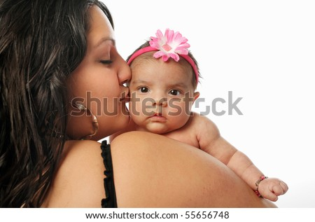 large Hispanic mother holding and kissing cute little newborn baby on the cheek on white background - stock photo