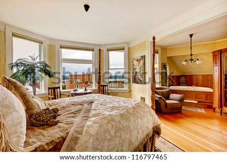 Large historical Inn room interior - bedroom with antique post bed. - stock photo