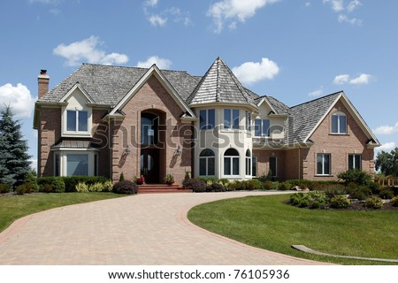 Large home in suburbs with turret and arched entry - stock photo