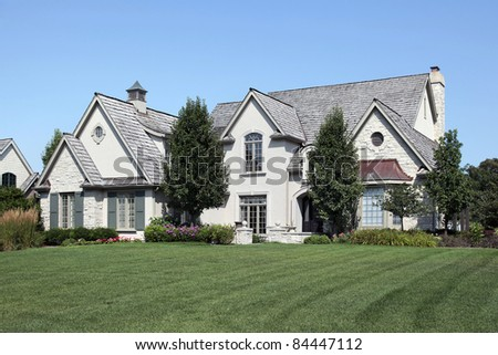 Large home with arched entry and cedar roof - stock photo