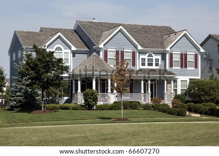 Large home with red shutters and cedar roof