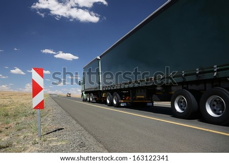 Large horse and trailer truck transporting cargo on the road - stock photo
