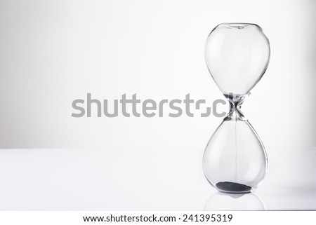 large hour glass sand timer with very little sand in there, time runs our quickly - stock photo