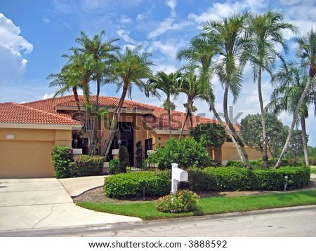 Large house in the tropics shaded by many palm trees. - stock photo