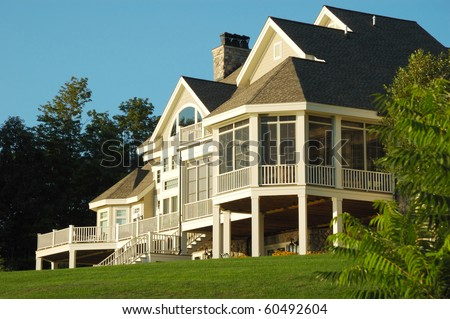 Large House Sitting on top of a Grassy Hill - stock photo