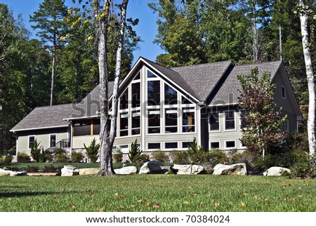 Large house with many windows and rocks in the landscape. - stock photo