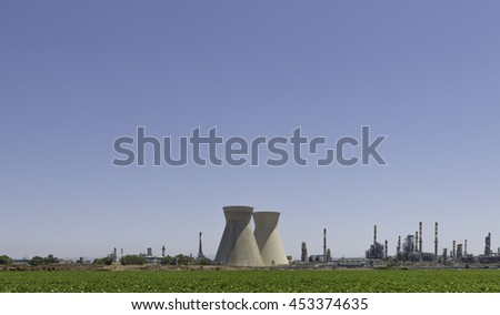 large industrial chimneys at refineries against green fields in Israel haifa