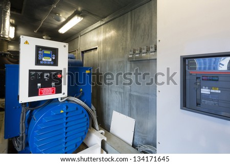 Large industrial diesel generator for backup power with control panel. - stock photo