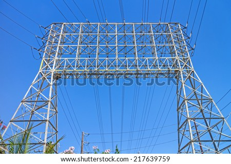 Large industrial electricity transmission tower or electricity pylon steel lattice grid structure, front perspective view. Array of wires, conductors and insulators. Blue sky background.  - stock photo