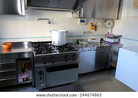 large industrial kitchen with big gas stove and the giant aluminum pot on the fire - stock photo
