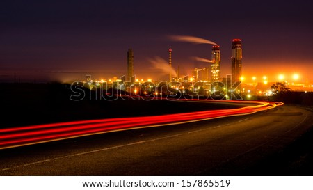 Large industrial plant at night, with smoking chimneys against the light trails of cars. DOF. - stock photo