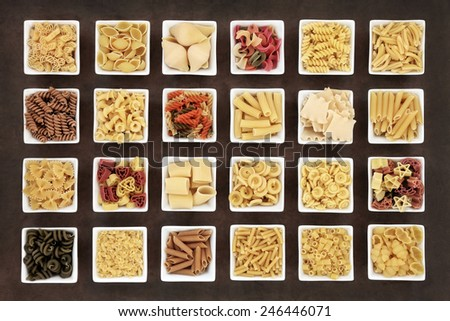 Large italian pasta dried food collection in square bowls over brown lokta paper background. - stock photo
