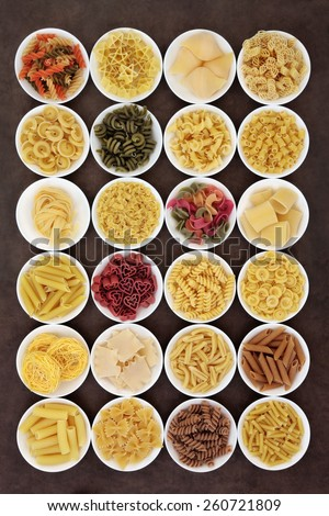 Large italian pasta dried food selection in round bowls over brown background. - stock photo