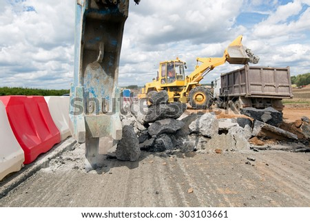 Large jackhammer breaking street asphalt paving during road construction works and wheel loader loading crushing asphalt pieces into dump truck - stock photo