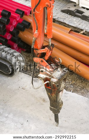 large jackhammer construction machine destroying pavement for repairing pipes in city street - stock photo