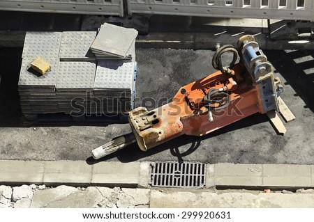 large jackhammer construction vehicle machine destroying pavement of a city street  close up   - stock photo