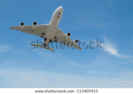 large jet aircraft on landing approach in a blue cloudy sky - stock photo