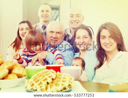 large joyful three generations family sits on sofa in livingroom at home