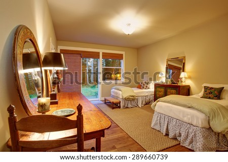 Large kids bedroom with twin beds and hardwood floor.