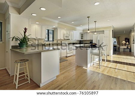 Large kitchen in luxury home with granite island top - stock photo