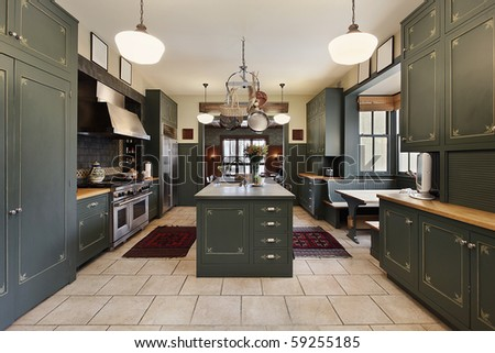 Large kitchen in luxury home with green cabinetry - stock photo