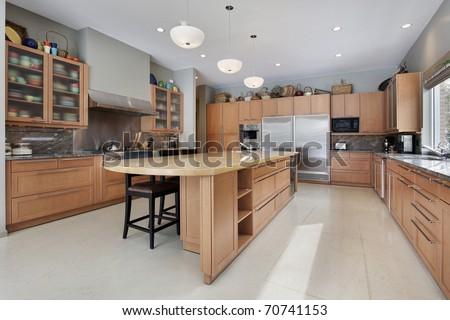 Large kitchen in luxury home with oak wood cabinetry - stock photo