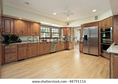 Large kitchen in suburban home with wood cabinetry - stock photo