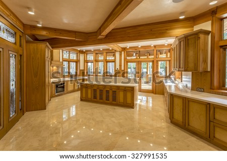 Large kitchen made of wood in eco house. Kitchen furniture and marble top and floor. The windows in the kitchen views the green garden. Design facilities new and modern. - stock photo