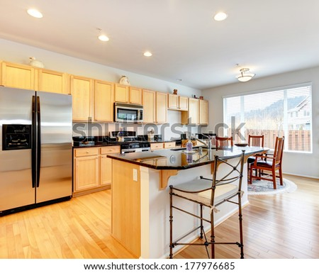 Large kitchen room with hardwood floor. Light tones storage cabinets with black counter tops