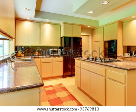 Large kitchen with honey wood and black appliances and red rug.