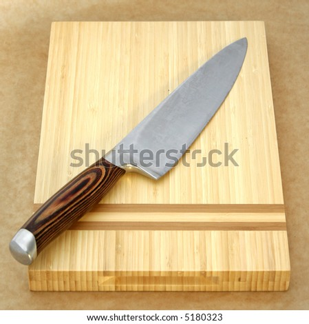 Large Knife on chopping board with rustic brown textured background - stock photo