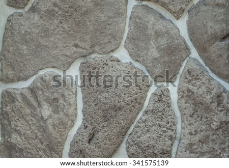 Large lava rock wall with white mortar and black/brown/gray/grey lava stones for use as a background, or for use as wallpaper - stock photo