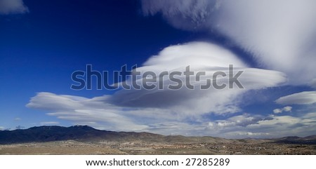 Large lenticular wind cloud resembling a UFO flying saucer over Peavine mountain near Reno, Nevada - stock photo