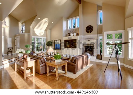 Large living room interior design with high vaulted ceiling and leather sofa set. Has telescope by the window - stock photo
