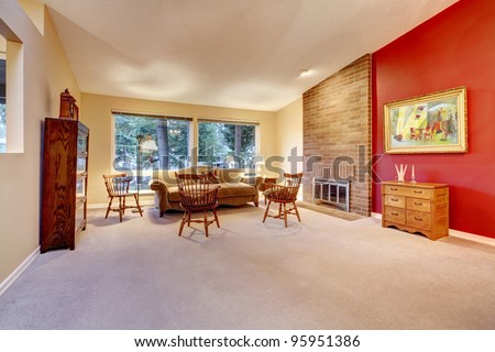 Large living room with red wall and brick fireplace. - stock photo