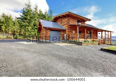 Large log cabin with porch and garage. - stock photo