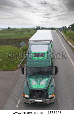 large lorry on countryroad in dramatic surrounding - stock photo