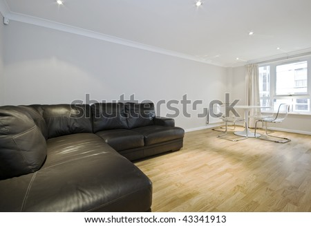 large lounge with massive leather sofa and plastic dining table with chairs - stock photo