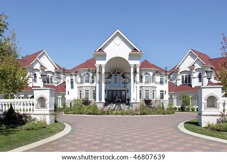 Large luxury home with arched entry and tiled roof - stock photo